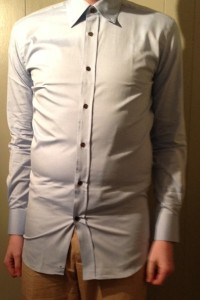 The image shows a man wearing a shirt which is too tight. Wearing shirts for large men with the correct chest sizing will avoid this problem.