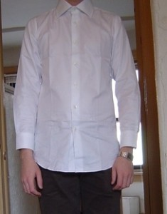 This image shows a man who has not bought of the shirts for long arms and is wearing a dress shirt that has too short sleeves for him.